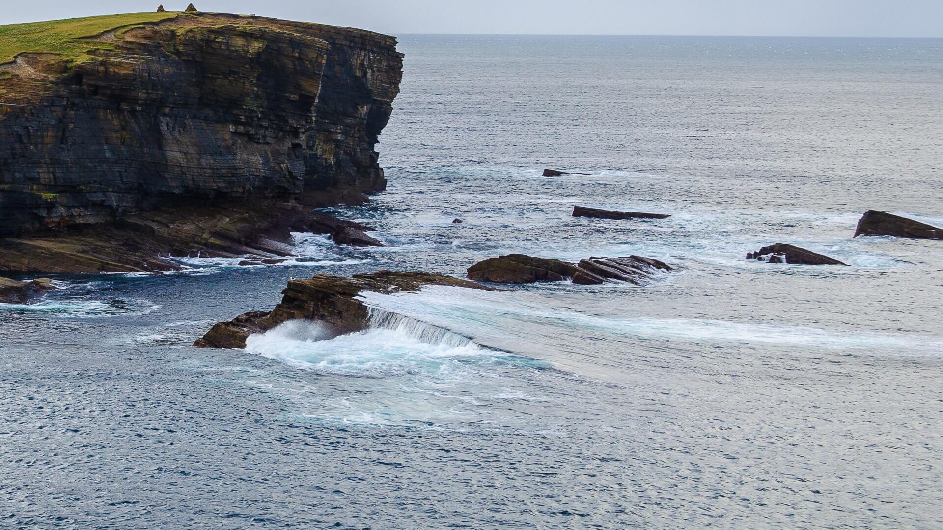 Vor den Klippen liegen Felstafeln im Meer