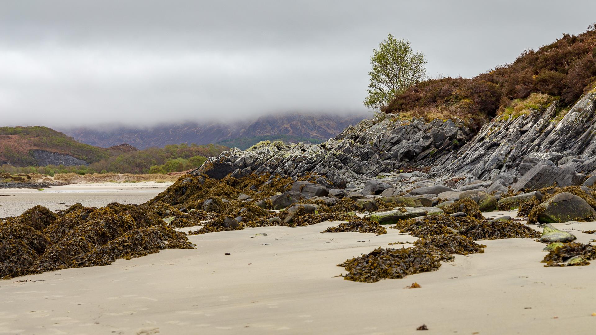 Aus dem Sandstrand erheben sich interessante Felsgesteine